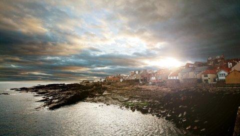 Город, берег, камни, солнце, свет, море, дома, облака, облачно