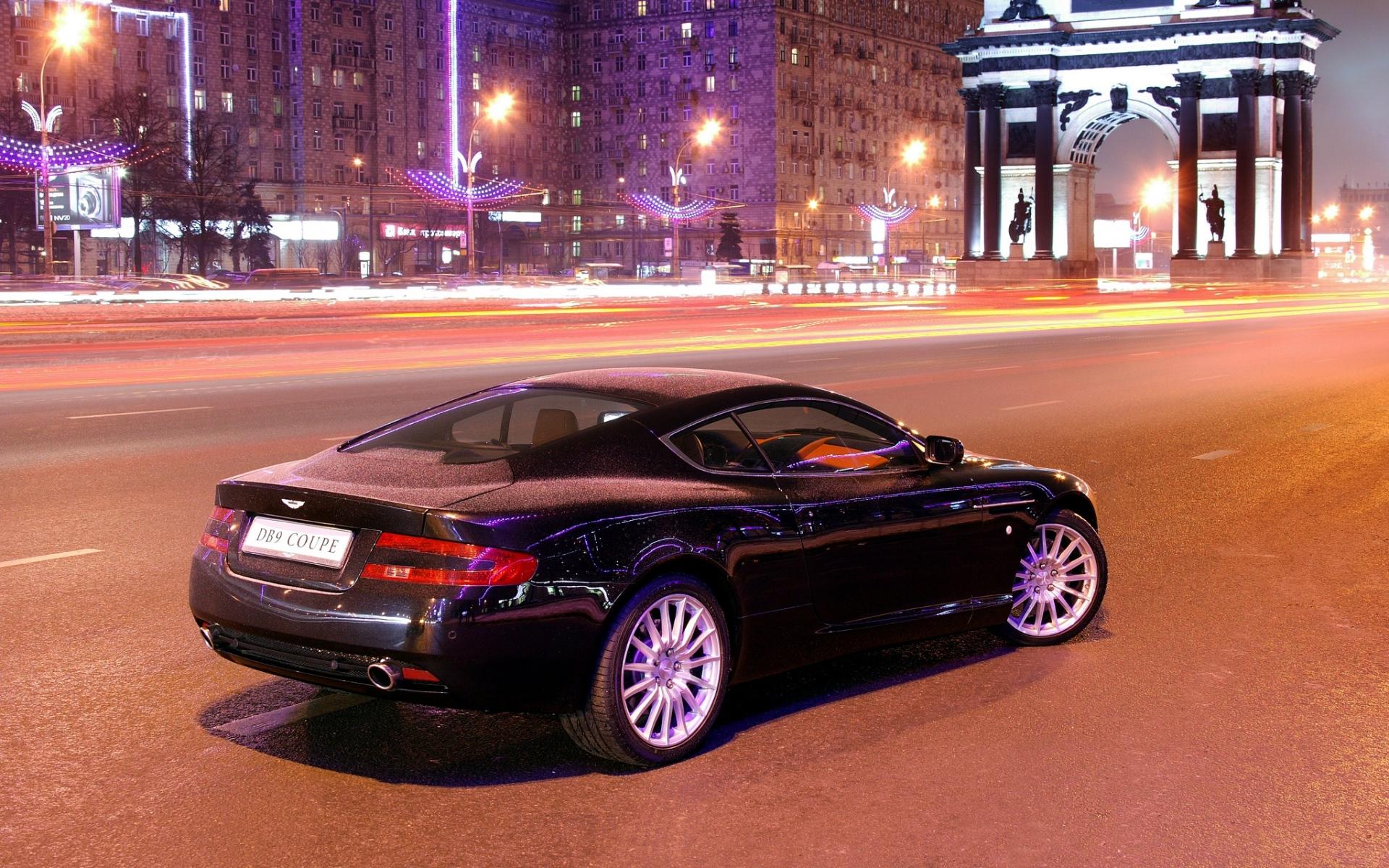 Картинки Aston martin, db9, черный, вид сбоку, стиль, автомобили, город, здания, фары, асфальт фото и обои на рабочий стол